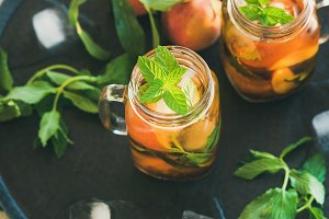 Summer refreshing cold peach ice tea in jars, square crop