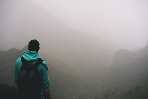 Traveler in hoodie in front of rural landscape with mountains and the ravine of Paul Valley. Santo Antao Island, Cape Verde