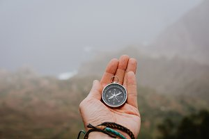 Looking at the compass to figure out right direction. Foggy valley and mountains in background. Santo Antao. Cape Cabo Verde