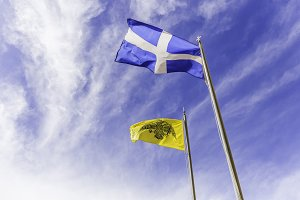 Greek and Byzantine flags waving on the air against cloudy sky