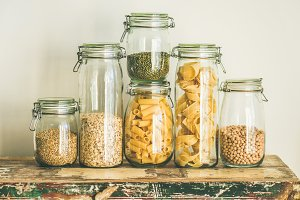 Uncooked cereals, grains, beans and pasta on rustic wooden table