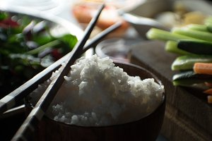 Chopsticks, rice and vegetables for cooking sushi top view. Asian cuisine