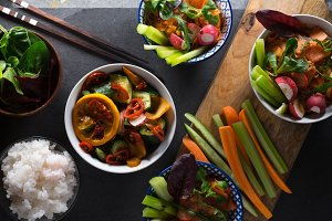 Rice, pickled vegetables in bowls and chopsticks close-up. Asian cuisine