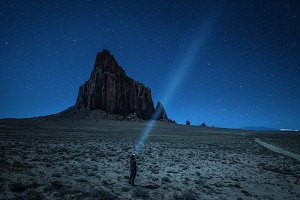 Hiker with a head lamp under the night sky near Shiprock, New Me