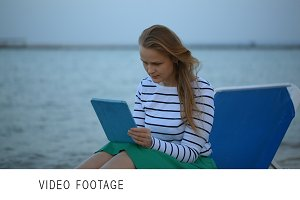 Woman with touchpad by the sea