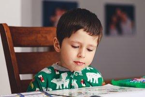 Pretty little boy reading a book