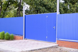 Fence and gate from sheets of blue corrugated metal.