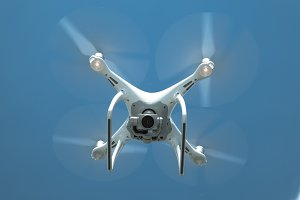 Drone DJI Phantom 4 in flight. Quadrocopter against the blue sky
