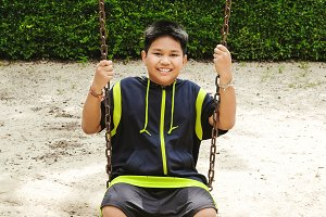Happy asian sport boy play on swing playground in Garden.