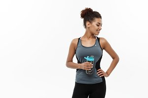Healthy and Fitness concept - beautiful African American girl in sport clothes holding water bottle after workout. Isolated on white studio background