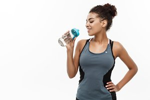 Healthy and Fitness concept - beautiful African American girl in sport clothes drinking water after workout. Isolated on white studio background