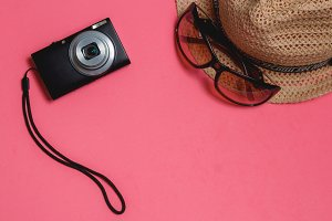 Travel Accessories: Sunglasses, Photo Camera, Brown Hat, on Pink Background. Top View Travel Concept with Copyspace.