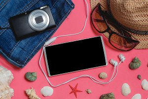 Smartphone, Clothes, Sunglasses, Photo Camera, Brown Hat, on Pink Background. Top View Travel Concept Mock up.