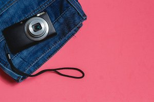Clothes, Photo Camera on Pink Background. Top View Travel Concept with Copyspace.