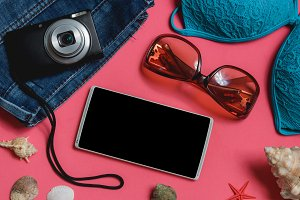 Smartphone, Swimsuit, Jeans, Sunglasses, Photo Camera, Seashell on Pink Background. Top View Travel Concept Mock up.