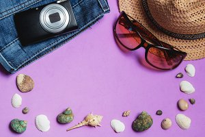 Jeans, Sunglasses, Photo Camera, Brown Hat, Seashells on Lilac Background. Top View Travel Concept with Copyspace.