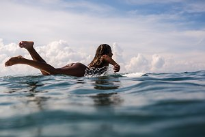 Beautiful young indonesian woman in bikini surfing wave in Bali on the background of blue sky, clouds and tropical beach