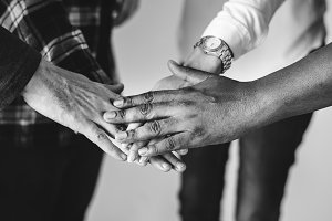 Diverse people joining hands