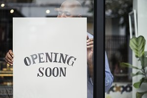 Man putting on store opening soon