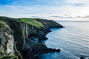 Scenic view of cliffs in Irish coast with green hills at sunset.