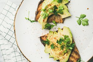 Flat-lay of avocado toast on plate over marble background