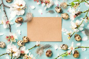 Easter background with eggs and almond flowers, paper in center