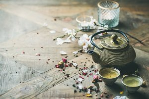 Iron teapot, cups, dried rose buds and candles, copy space