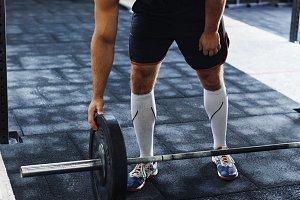 Bodybuilder adding weight to barbell