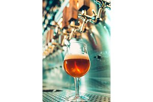 Beer craft. Bar table. Steel taps. Shiny taps. Glass of beer