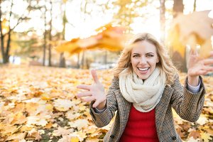 Woman in checked coat sitting in autumn park