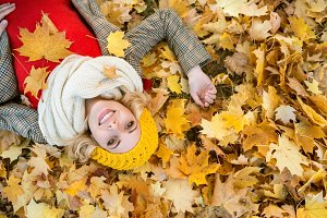 Woman in checked coat lying in autumn park