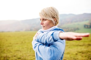 Young blond runner outside in sunny nature, stretching arm