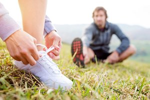 Couple running in autumn nature, stretching, tying shoelaces
