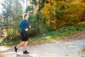 Young handsome runner outside in sunny autumn nature