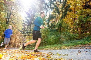 Beautiful couple running outside in sunny autumn forest