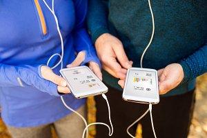 Unrecognizable running couple with smart phones and earphones