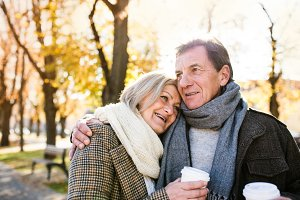 Beautiful senior couple hugging in park, drinking coffee. Autumn