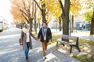 Senior couple on a walk in park. Autumn nature.