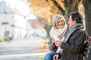 Senior couple sitting on bench, drinking coffee. Autumn nature.