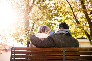 Senior couple sitting on bench, autumn nature. Rear view