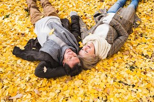 Active senior couple in autumn park lying on the ground