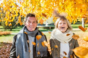 Active senior couple in autumn park throwing leaves