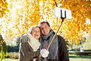 Senior couple taking selfie in park. Sunny autumn nature.