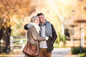 Beautiful senior couple hugging in park. Sunny autumn nature.