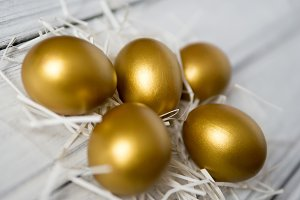Golden Easter eggs on a wooden table