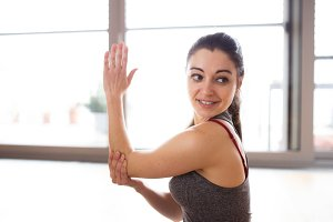 Young woman exercising at home, stretching arms.