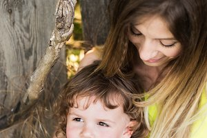 Beautiful mother with her little son against old wooden fence.