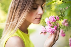 Beautiful blond woman smelling pink rose flowers. Sunny summer.