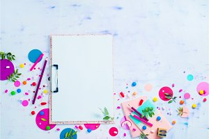 Feminine background blank pages clip note, pink notepads, candies and confetti on a white wooden background. Colorful planning party concept with copy space.