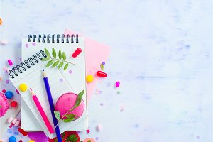 Blank lined notepads with colorful pencils, sweets and pink macaron cookie on a light background with copy space. Party planning fun concept.